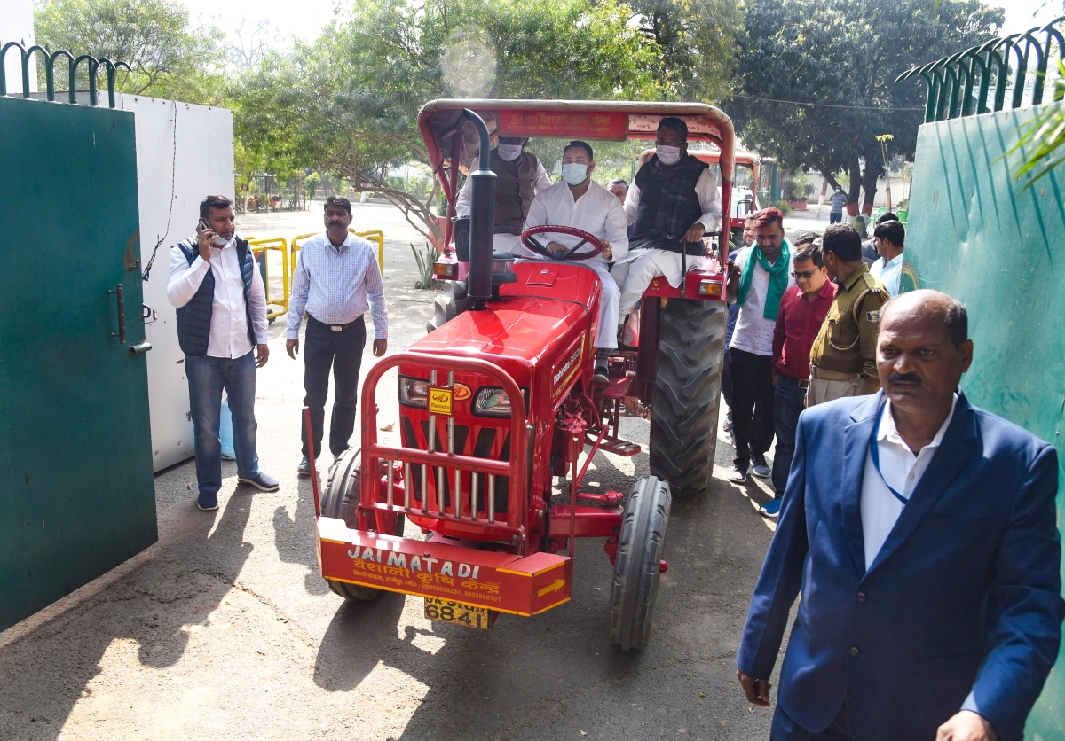 RJD leader Tejashwi Yadav rides a tractor during a protest against the new farm laws amid the Budget Session of Bihar Assembly