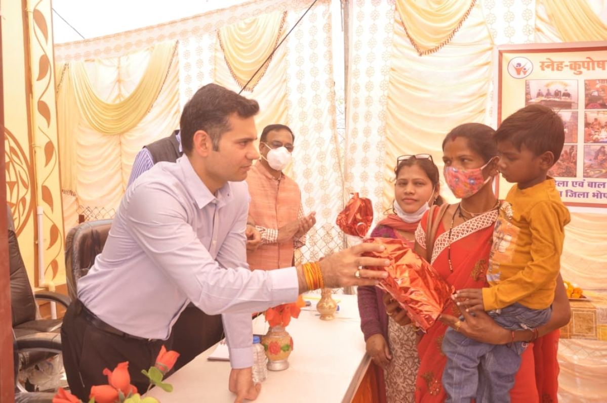 Collector Avinash Lawania distributes protein and multivitamins to kids and women at Sneh-Suposhan programme on Sunday.