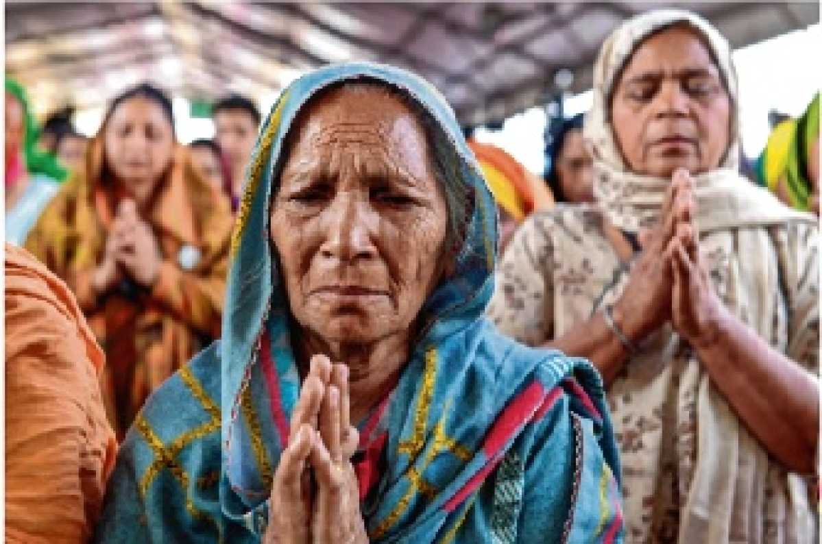 A woman pays a tribute to  farmers who lost their lives  during the protest.