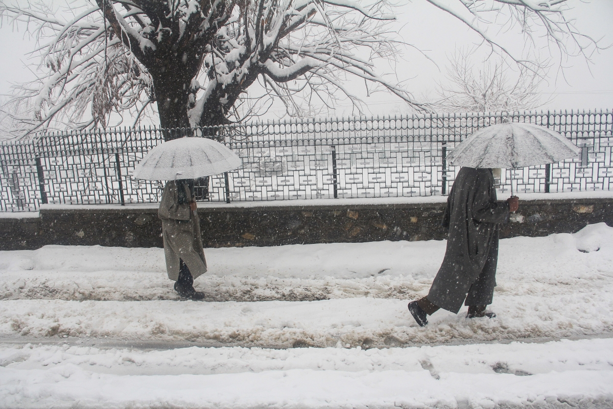Pedestrians walk across a snow-covered road in Baramulla District of Jammu and Kashmir, on Saturday.