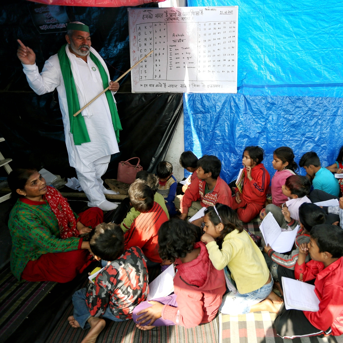Farmer leader Rakesh Tikait teaches children at makeshift school at protest site