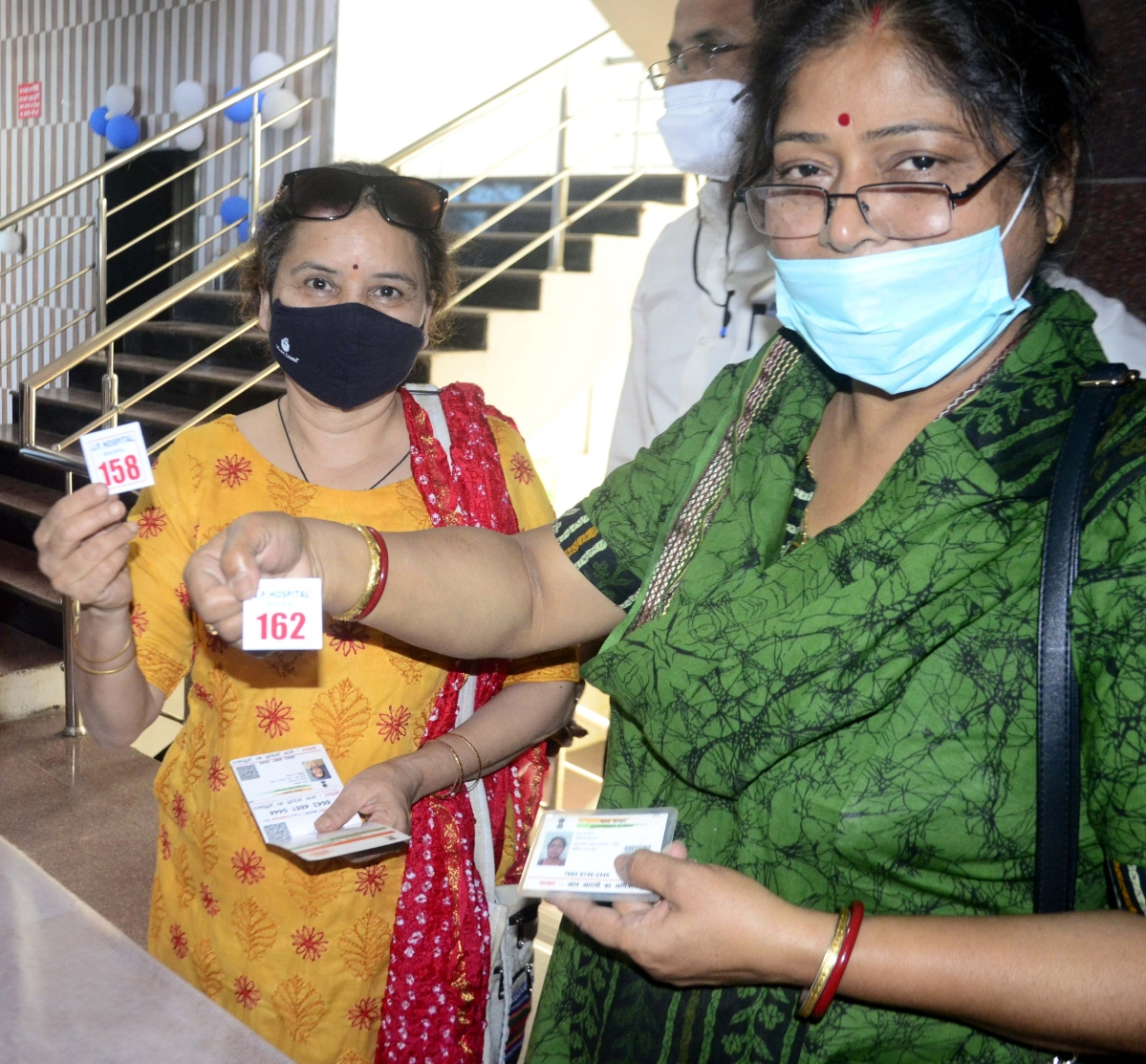 People coming for vaccine show their token number at JP hospital in Bhopal