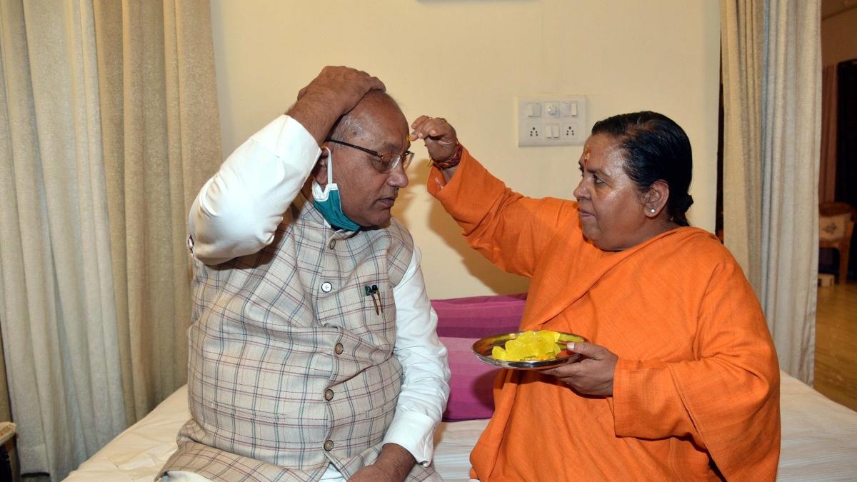 BJP leader Uma bharati applies tilak to Vidhan Sabha speaker Girish Gautam at her residence on Tuesday.