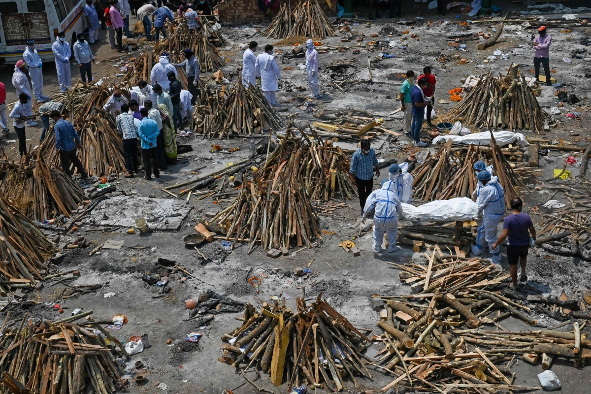 Family members and relatives prepare the funeral pyre of victims who died of the Covid-19 coronavirus during mass cremation held at a crematorium in New Delhi on April 27, 2021