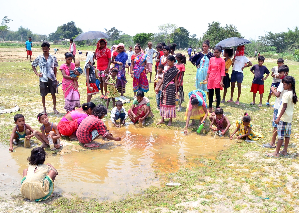 "Villagers collect the water seeping out of the cracks on a paddy field caused due to a high-intensity earthquake, at Ghogra Village in Sonitpur district Wednesday. The villagers stored the water out of superstition that it is ""Water of God."""