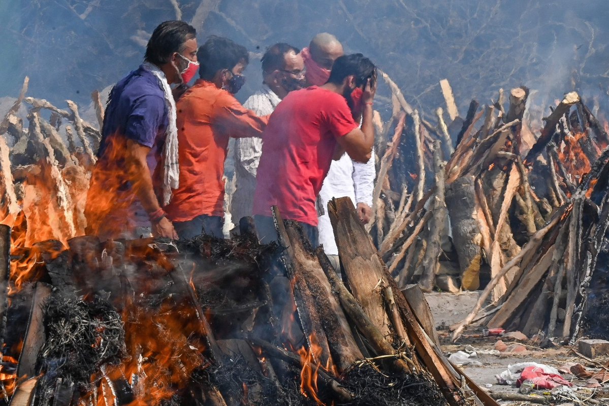 A man reacts as he performs the last rites of his relative amid the funeral pyres of victims who died of the Covid-19 coronavirus during mass cremation held at a crematorium in New Delhi on April 27, 2021.