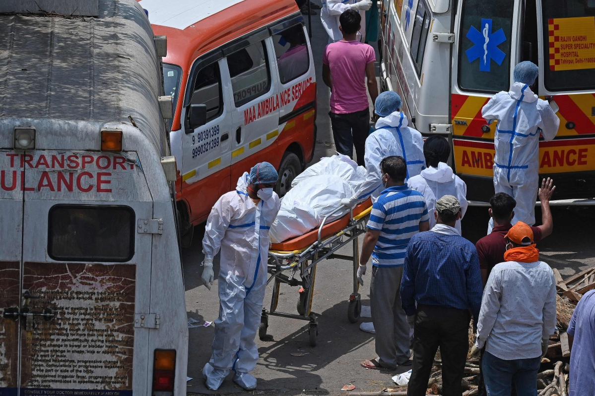 Family members and ambulance workers in PPE kits (Personal Protection Equipment) carry the bodies of victims who died of the Covid-19 coronavirus at a crematorium in New Delhi on April 27, 2021.
