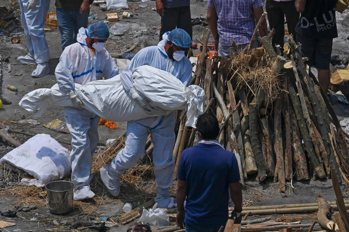 Family members and ambulance worker wearing PPE kit (Personal Protection Equipment) carry the bodies of the patients who died of the Covid-19 coronavirus at a cremation ground in New Delhi on April 27, 2021.