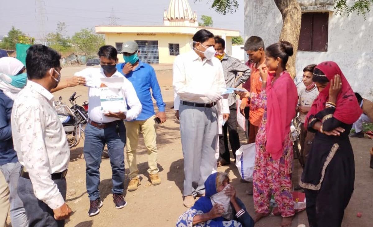 Prof. Ramdev Bhardwaj distributes masks to common people in a village.