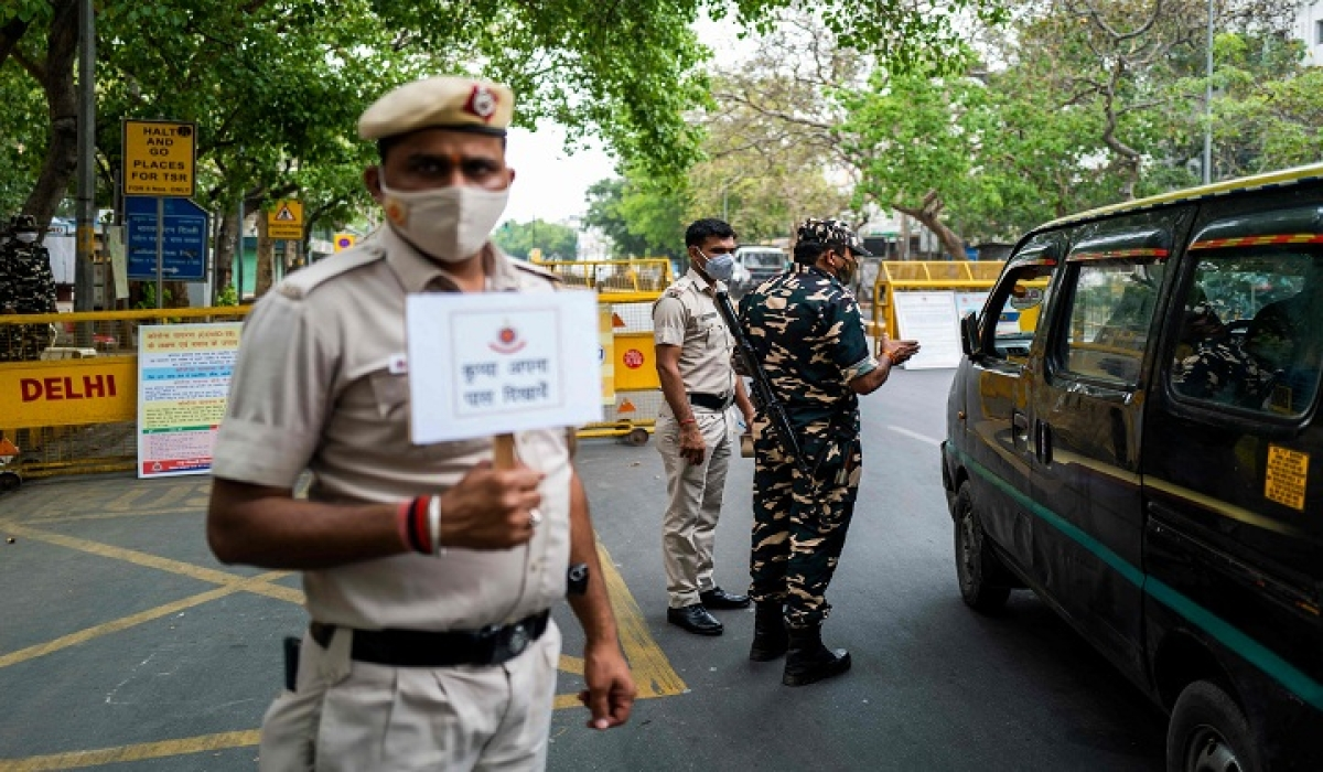 Policemen put up a barrier, as Delhi imposed a week-long lockdown beginning April 19 to control the surge in New Delhi on Tuesday.