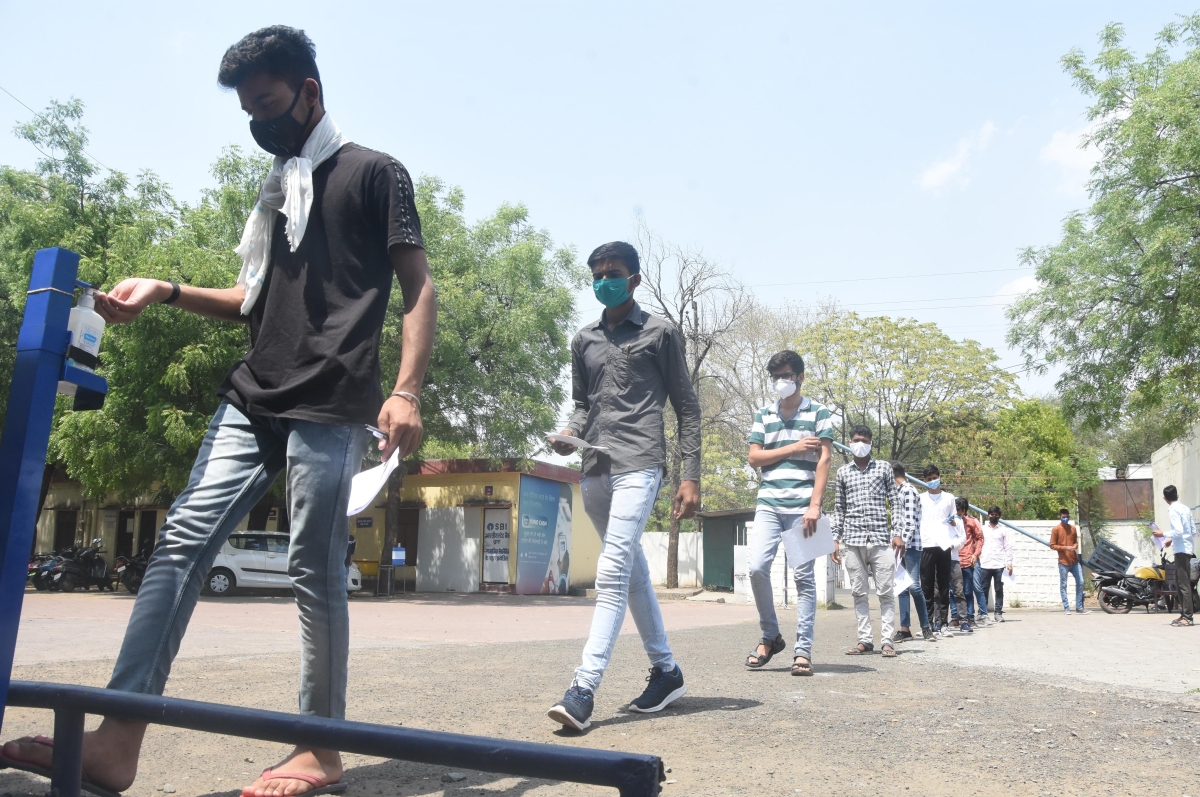 One of the candidates appearing for UPSC preliminary examination on Sunday, sanitizes before entering examination hall.