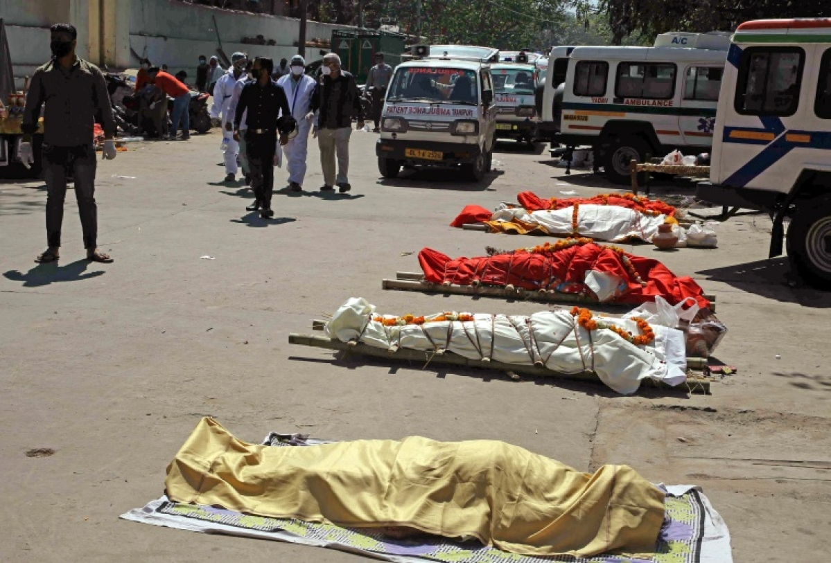 Dead bodies of the victims lay on the ground who died due to COVID-19, at Nigambodh Cremation Ground in New Delhi on Saturday
