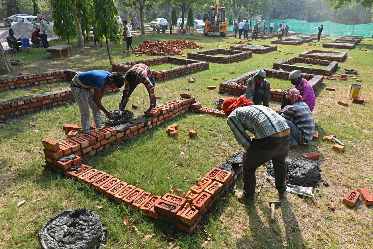 Workers are seen constructing makeshift platforms for funeral pyres inside the premises of a crematorium in New Delhi on April 27, 2021