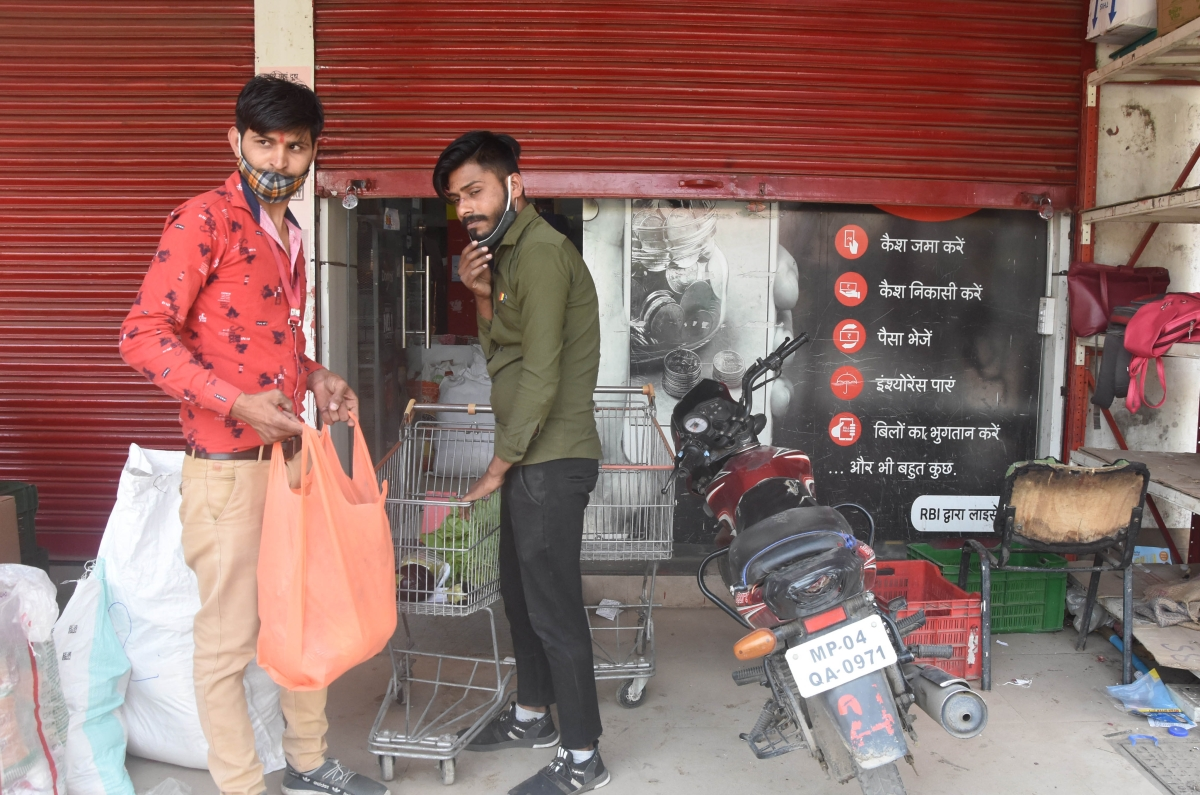 A trader in Bhopal supplies essential items to his customer with half his shutters down during the lockdown on Wednesday.