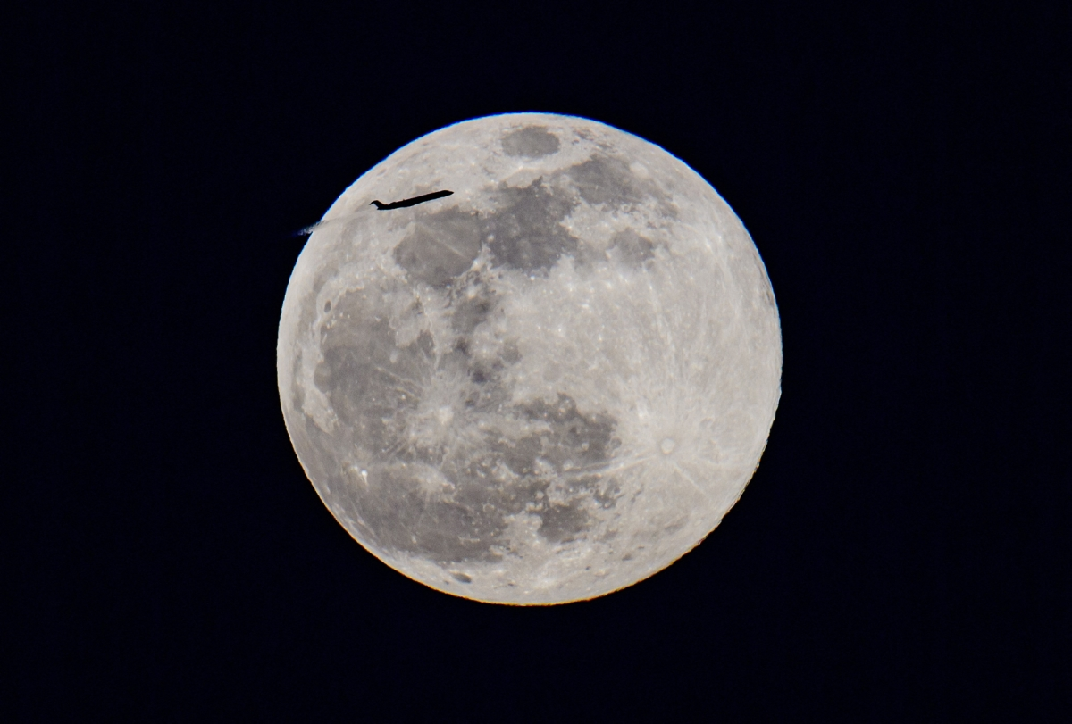 A plane is seen flying across the full moon of April, called the Super Pink Moon, rises over Manhattan, New York on April 26, 2021.