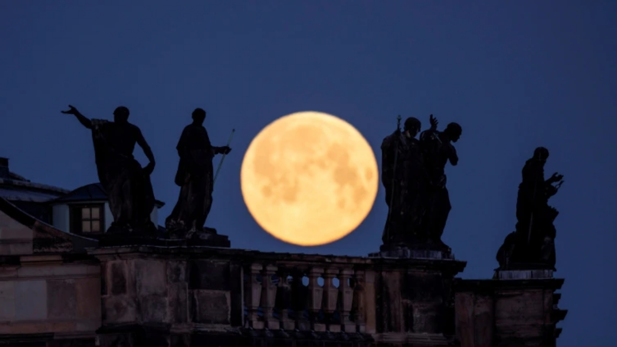 Supermoon is seen behind the sculptures on the roof of the cathedral in Dresden.