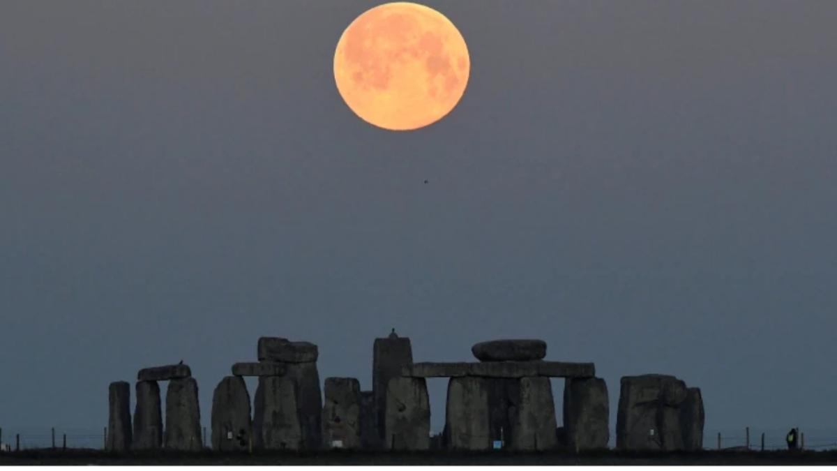 Supermoon sets behind Stonehenge stone circle near Amesbury, Britain.