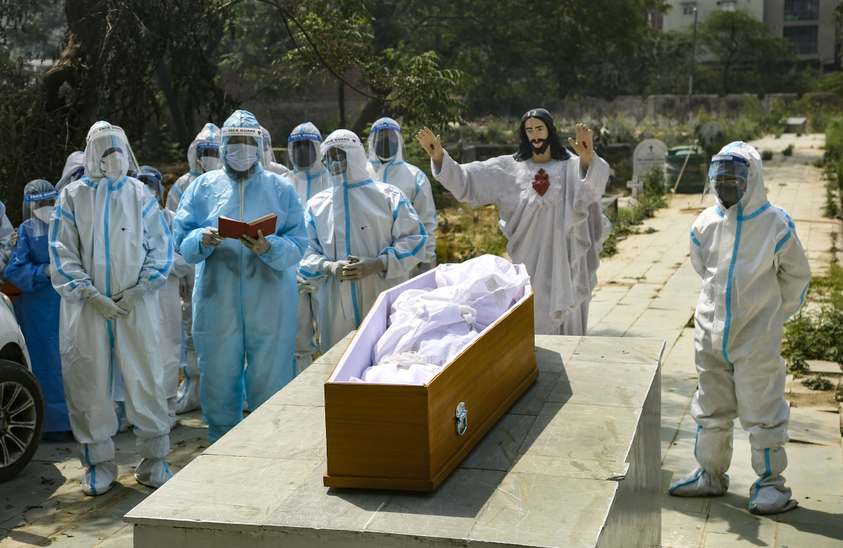 A priest reads the bible during the last rites of a person who died of coronavirus, at a Christian cemetery in New Delhi, Tuesday, April 27, 2021.