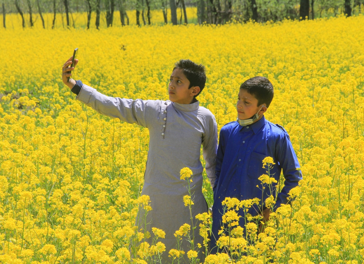 Children take selfies in a blossoming mustard field on the outskirts of Srinagar, Kashmir.