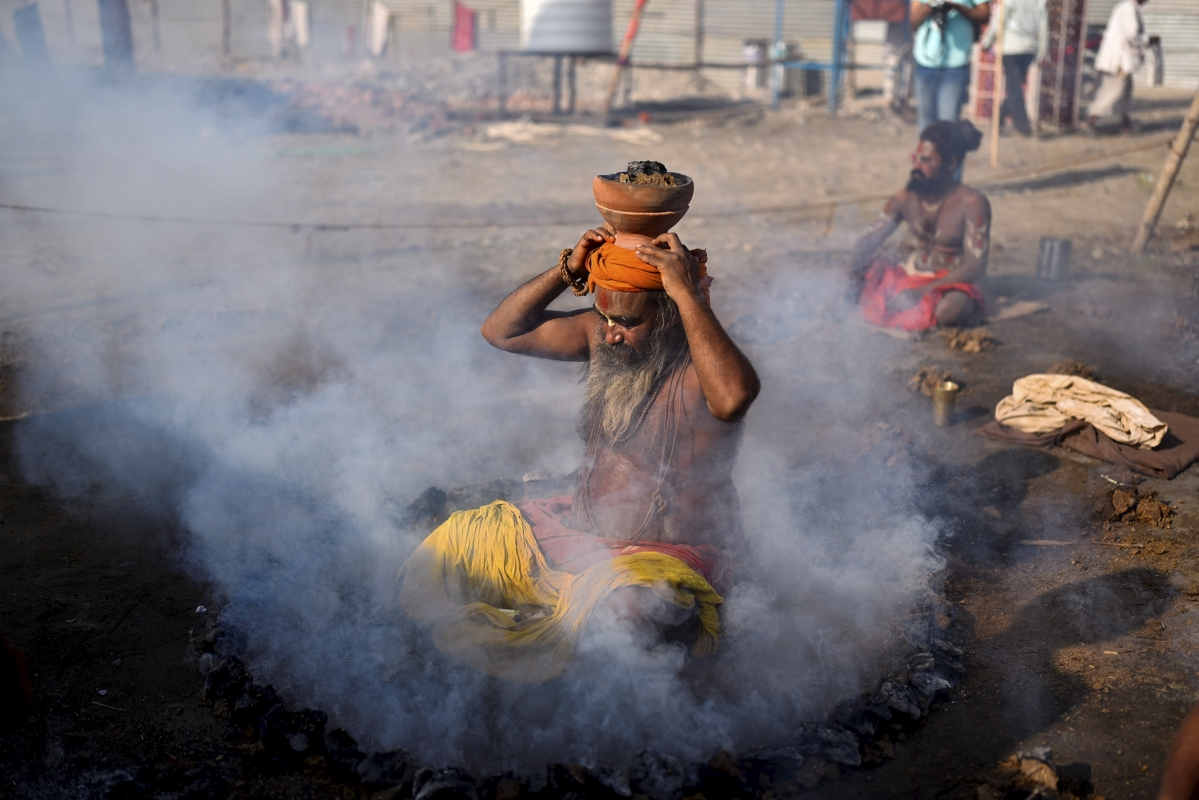 Haridwar: Sadhus performs ritual during morning prayers at Kumbh Mela 2021, amid surge in Covid-19 cases across country, in Haridwar, Tuesday, April 13, 2021.