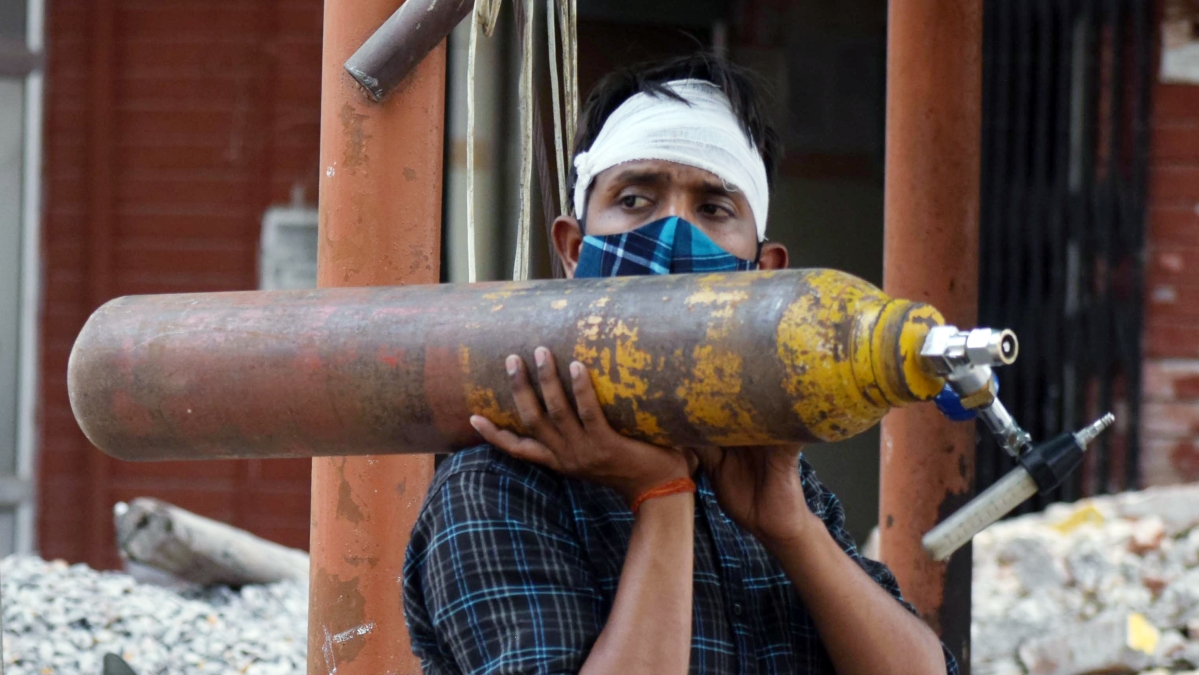 A worker carries an oxygen cylinder to COVID-19 care ward amid the rise in cases, at Swaroop Rani Nehru hospital in Prayagraj on Friday | Representational