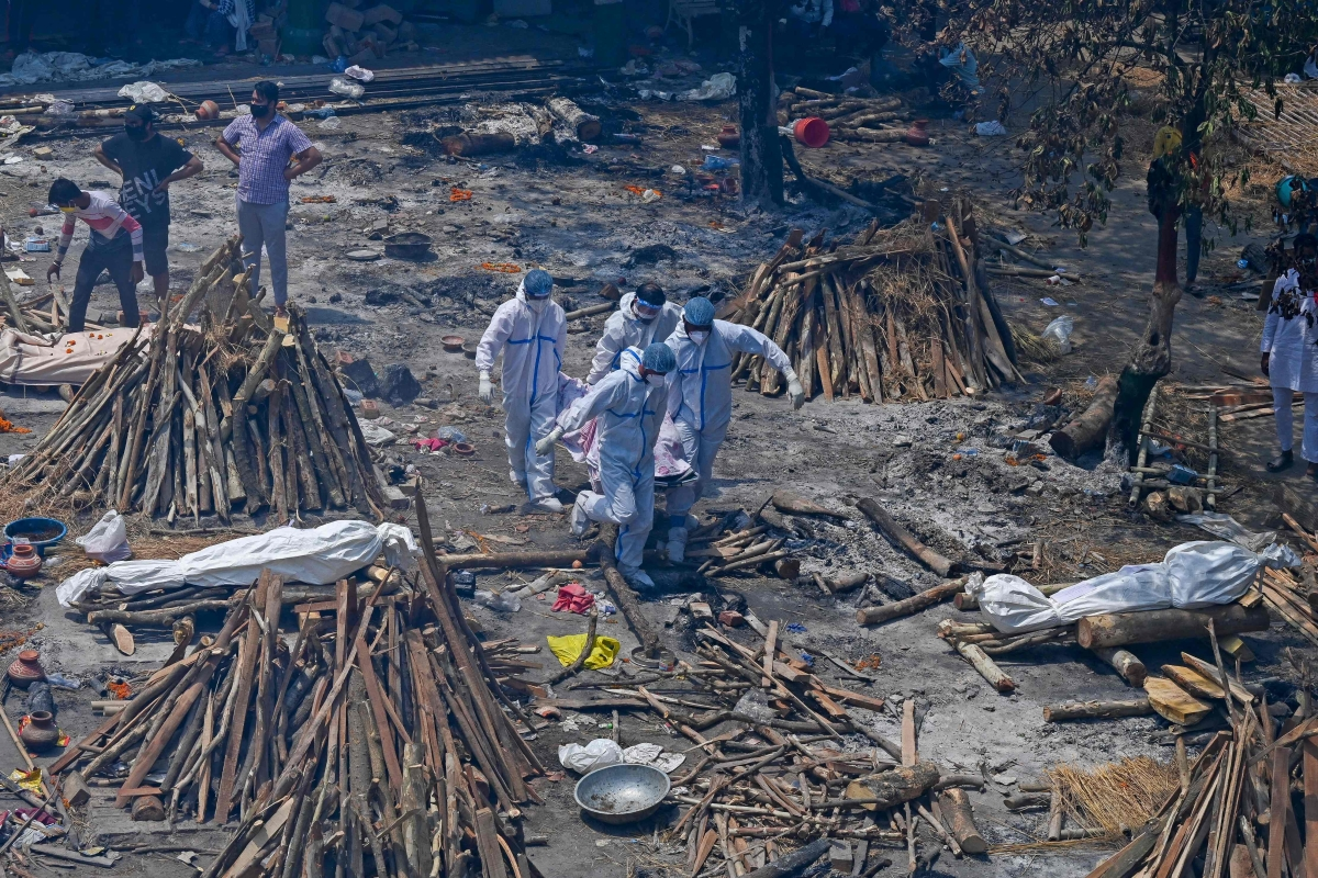 Family members and relatives perform the last rites amid the funeral pyres of victims who died of the Covid-19 coronavirus during mass cremation held at a crematorium in New Delhi on April 27, 2021.