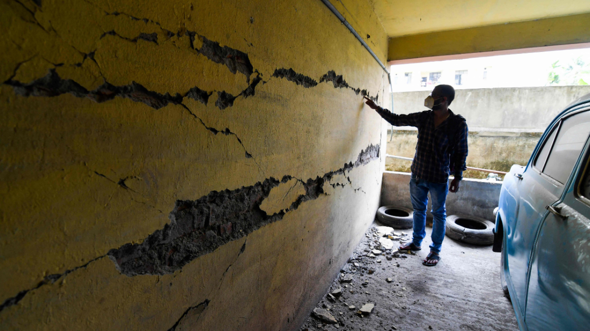 A man looks at cracks on a wall at an apartment building in Guwahati on April 28, 2021, after a strong earthquake hit Assam in northeastern India, damaging buildings