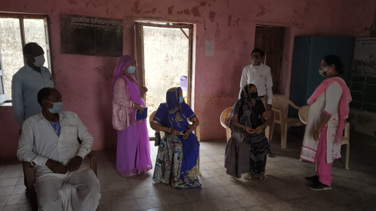 People waiting for turn to get vaccinated at vaccination centre in Sardarpur village of Dhar district on Monday
