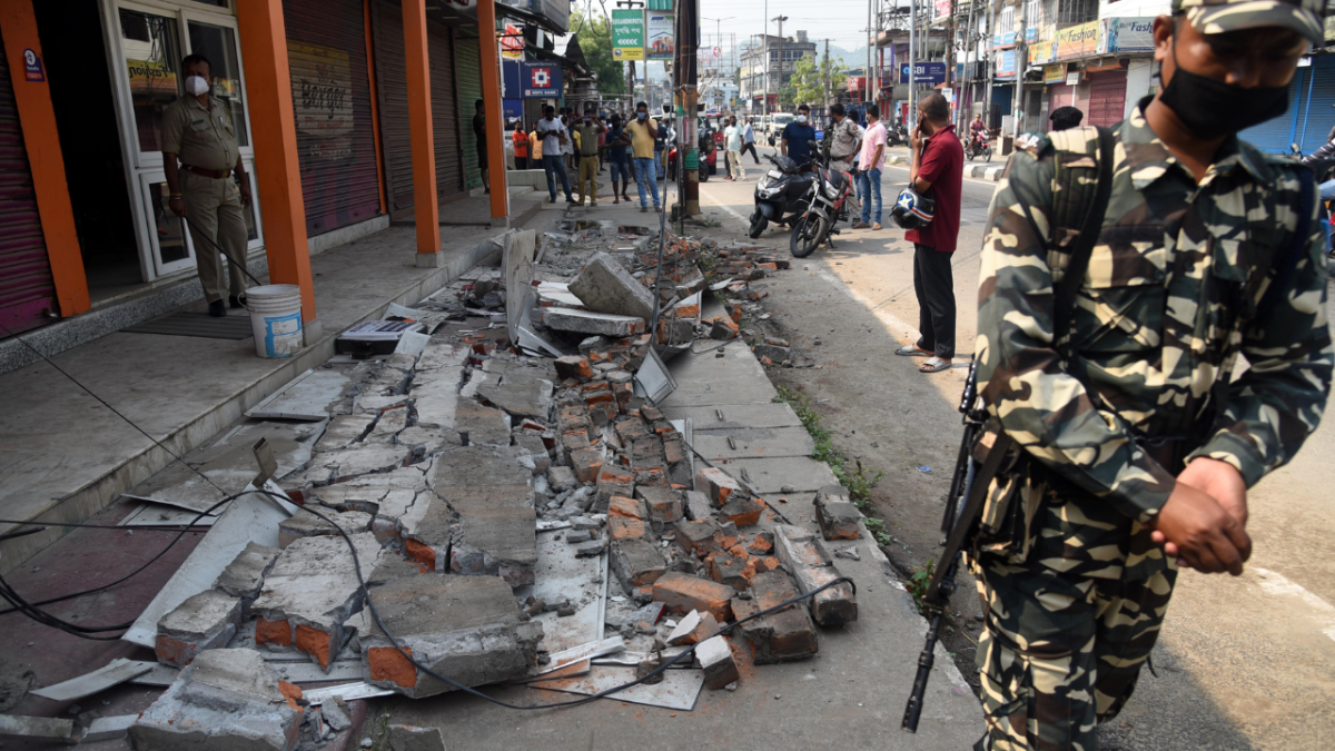 A CRPF personnel stand guards near an earthquake-damaged building at Bhetapara in Guwahati, Wednesday, April 28, 2021.