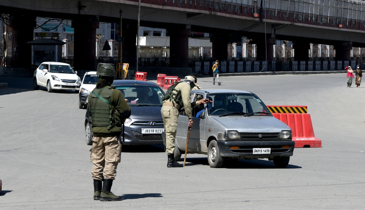 Police personnel stop vehicles to check the documents and curfew-pass on the first day of the weekend curfew in the state amid the rise in COVID-19 cases, in Srinagar, Kashmir.