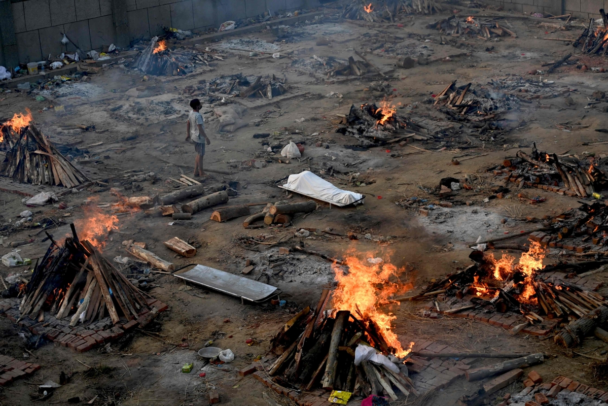 A man stands amid burning pyres of victims who lost their lives due to the Covid-19 coronavirus at a cremation ground in New Delhi on April 26, 2021.