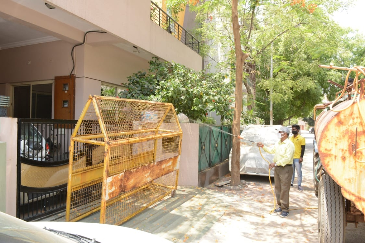 A Ujjain Municipal Corporation staff sprays sanitiser on the house of a corona patient in Ujjain on Wednesday