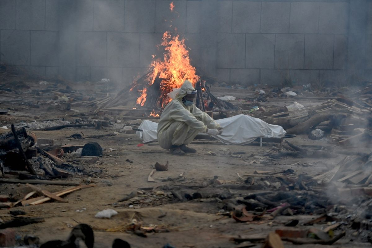 A man sits next to the body of a victim who died of the Covid-19 coronavirus besides the burning pyre of another victim at a cremation ground in New Delhi on April 26, 2021.