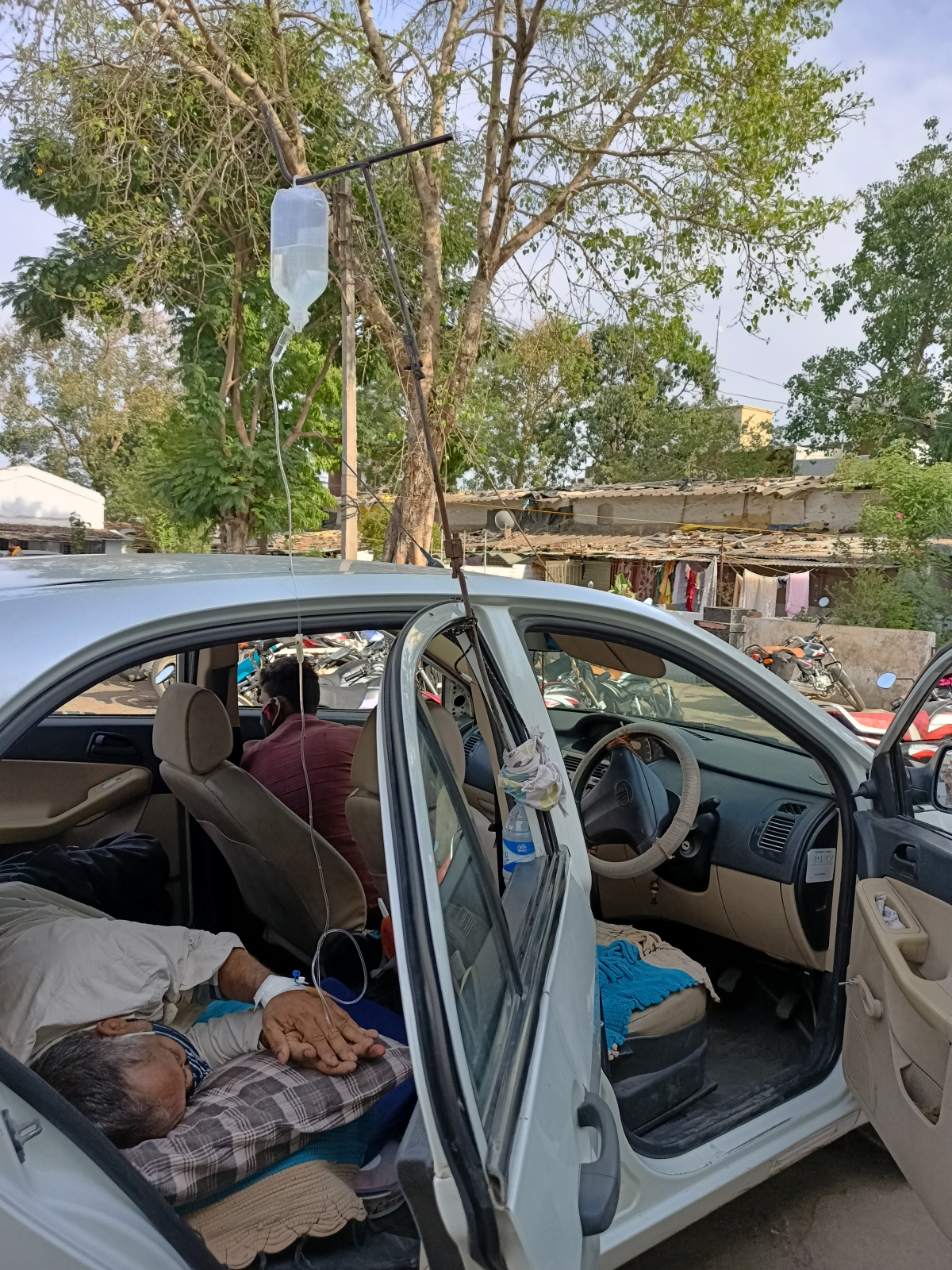 Patient getting treatment in a car outside Sardarpur CHC on Sunday.