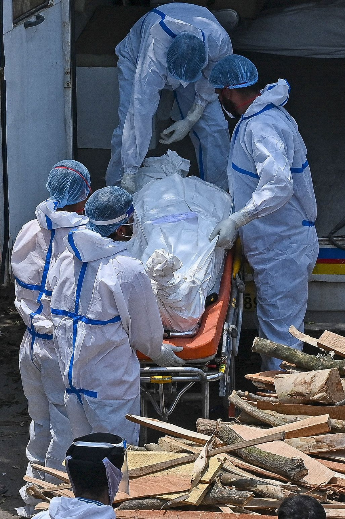 Family members and ambulance workers wearing PPE kits (Personal Protection Equipment) carry the bodies of patients who died of the Covid-19 coronavirus during mass cremation held at a crematorium in New Delhi on April 27, 2021.