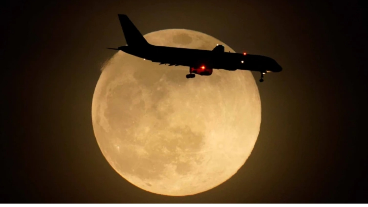 An airplane flies by as supermoon rises in Kentucky, USA.
