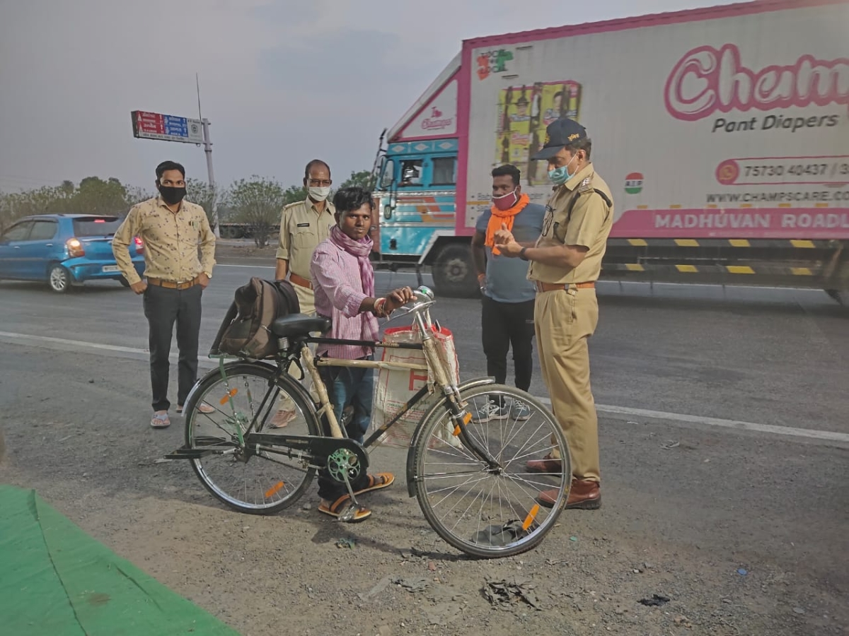 Police providing slippers and food to a migrant worker who was returning home to Bihar on his bicycle.