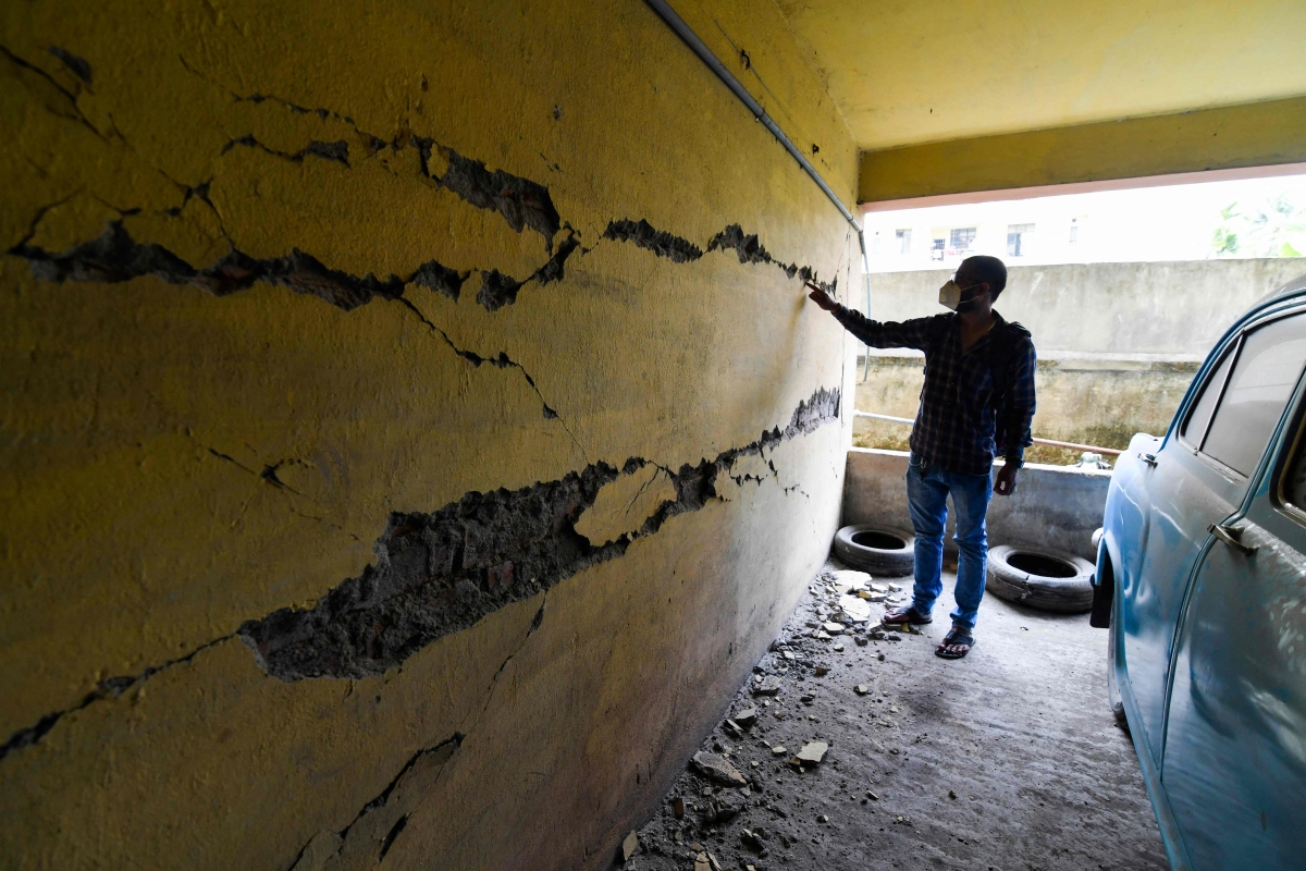 A man looks at cracks on a wall at an apartment building in Guwahati on April 28, 2021, after a strong earthquake hit Assam in northeastern India, damaging buildings.