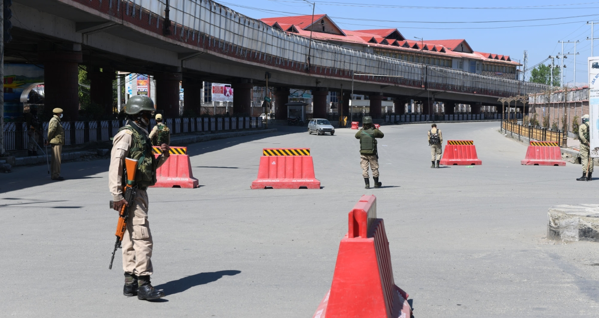 Paramilitary personnel stand guard at a deserted street during a weekend curfew imposed in Srinagar, Kashmir, amid a countrywide spike in coronavirus cases.