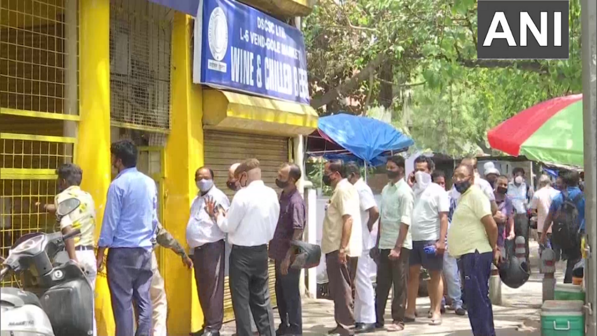 People queue up outside a liquor shop in Gole Market area after Delhi govt announced a 6-day lockdown in Delhi.