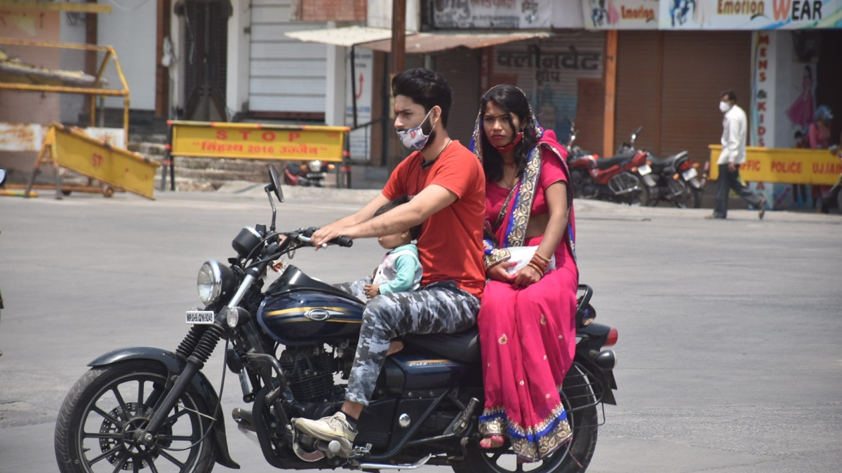 A young couple move with their little one throwing corona protocols to the winds in Ujjain on Thursday.