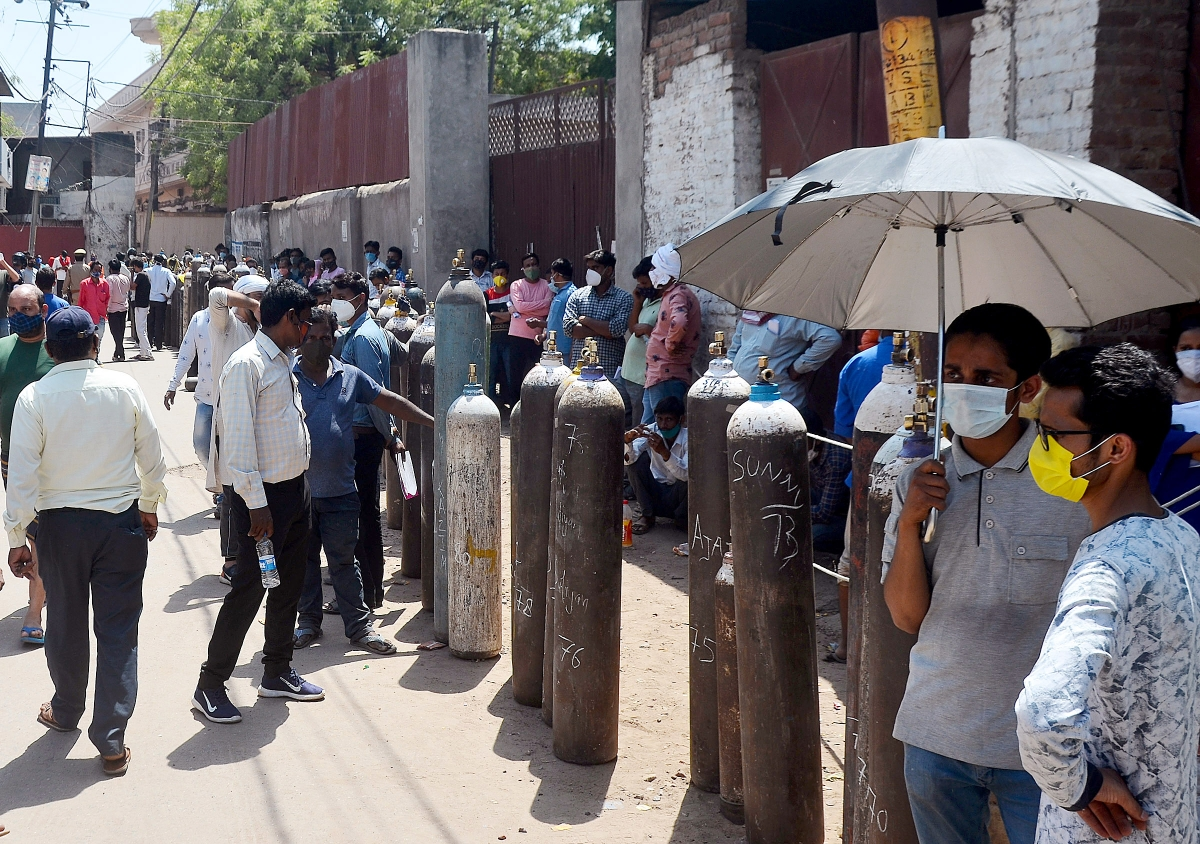 Relatives of COVID-19 patients stand in a queue to get refilled their Oxygen cylinders at Awadh Oxygen Refilling Centre, Talkatora, in Lucknow on Saturday.