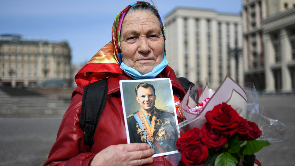 A Russian Communist party supporter holding a portrait of Soviet cosmonaut Yuri Gagarin, the first man in space, stands on Moscows Manezhnaya square prior to a flower laying ceremony at the grave of Yuri Gagarin by the Kremlin wall on the 60th anniversary of his flight, on April 12, 2021.