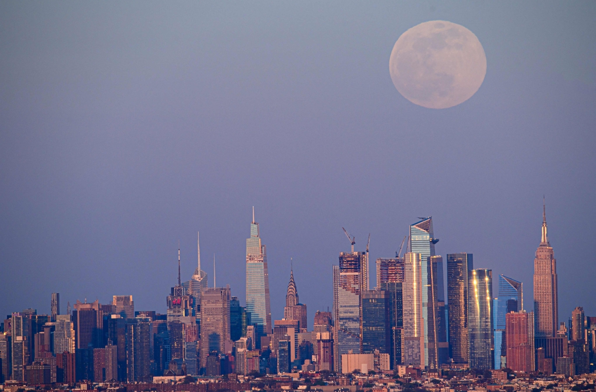 The full moon of April, called the Super Pink Moon, rises over the skyline of Manhattan on April 26, 2021.