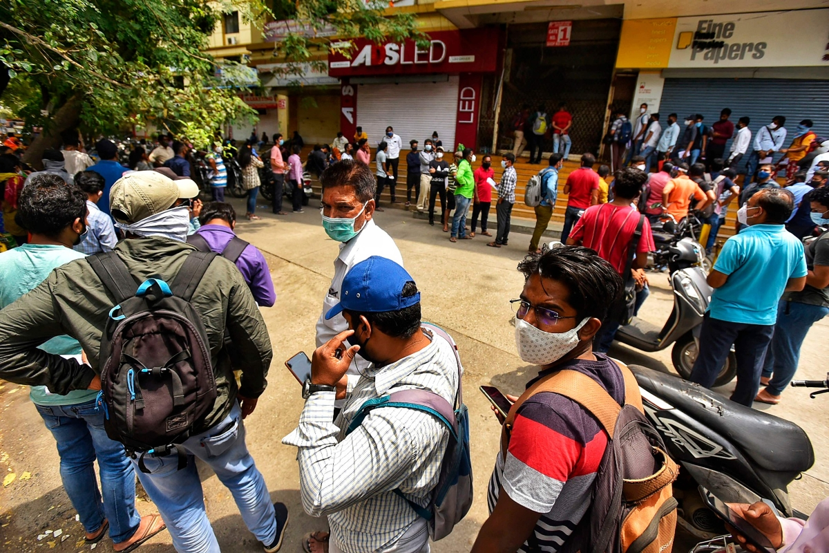 People queue outside the Chemists Association office for Remdesivir, an antiviral drug, in Pune on April 9, 2021 as India surged past 13 million coronavirus cases.