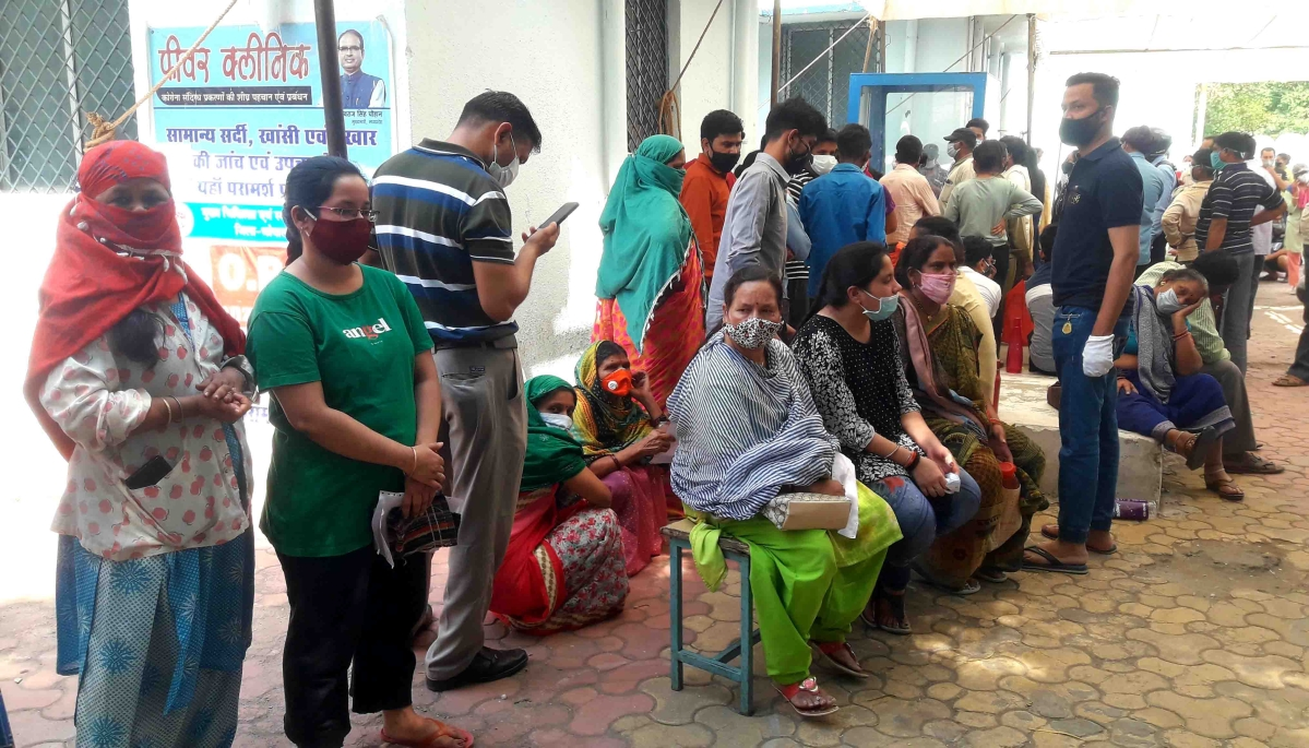 People wait for their turn for testing and sampling at a fever clinic in Bhopal on Tuesday.