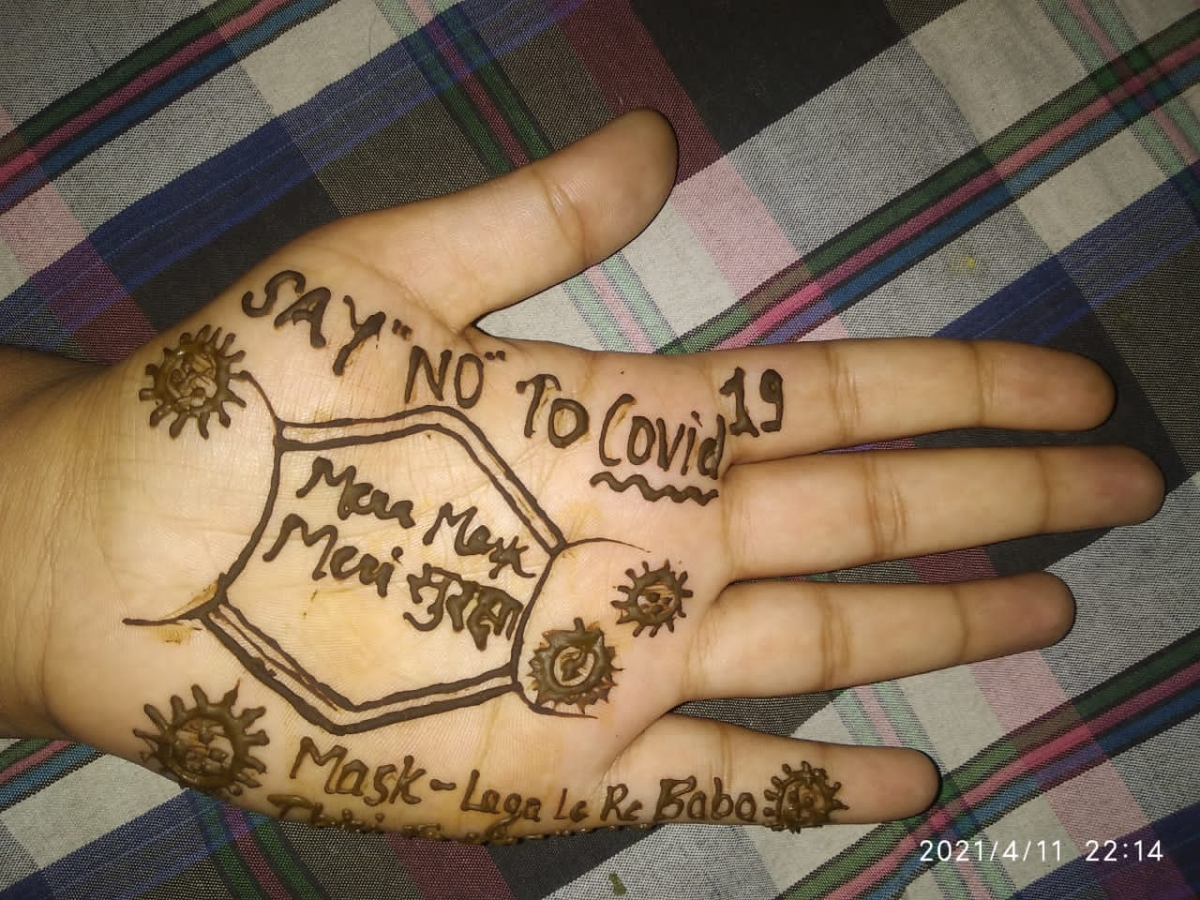 An NSS volunteer giving out message on corona vaccination through henna design on hand