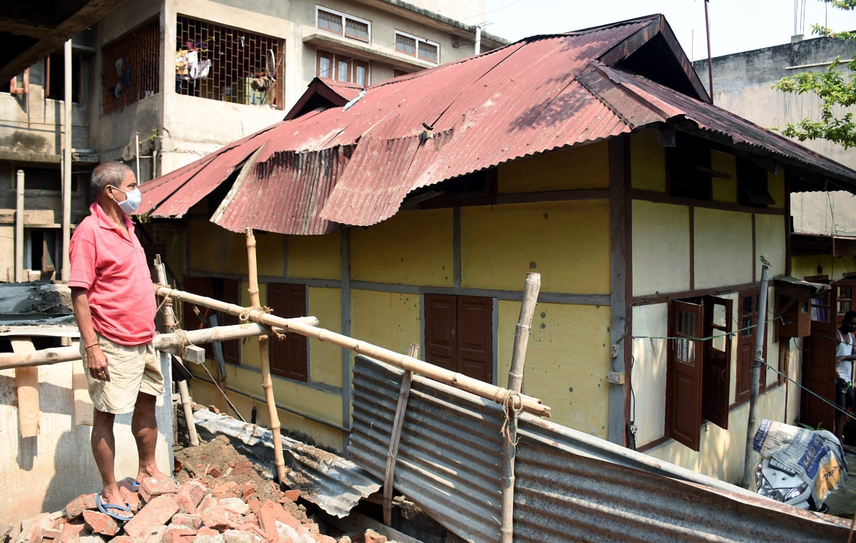 A man seen standing looks on the damaged roof of a house after the earthquake, at Ganeshguri in Guwahati on Wednesday.