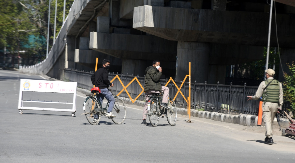 Security personnel stop commuters during the weekend curfew imposed in the wake of rising Covid-19 cases, in Srinagar, Kashmir.