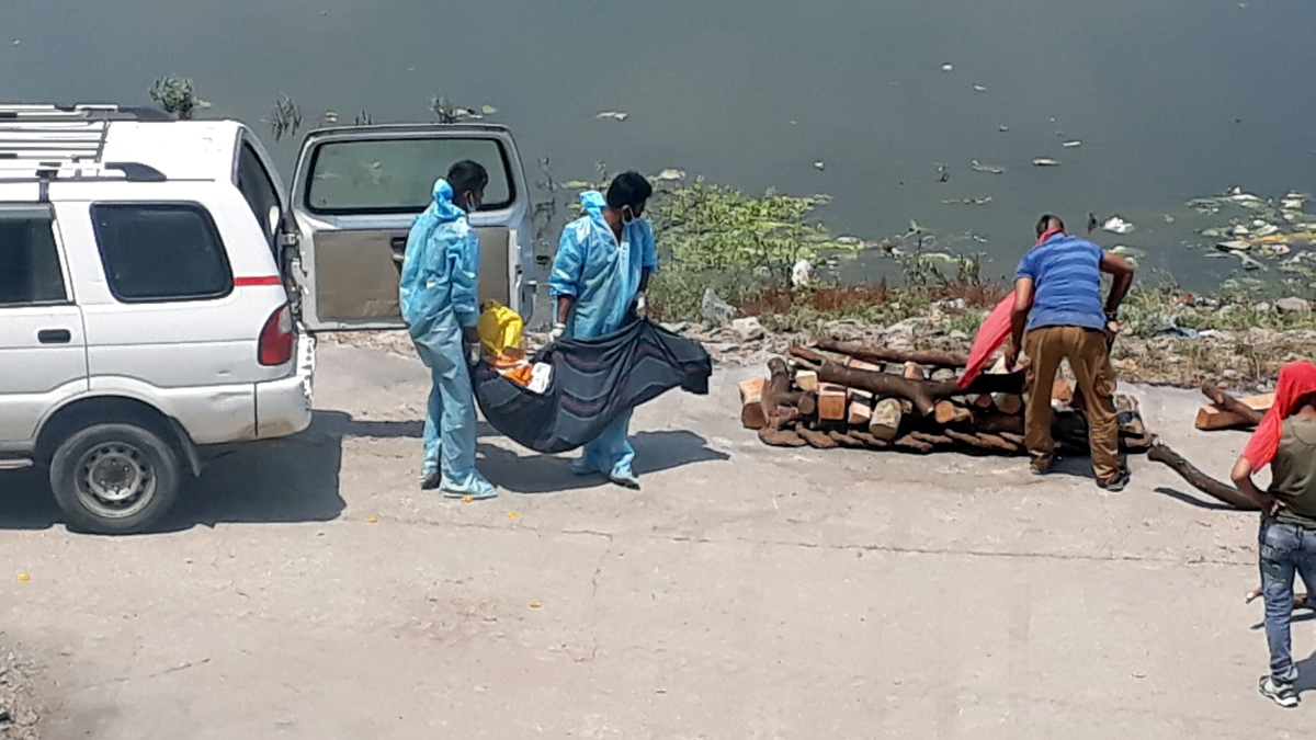 Crematorium staff perform last rites of a corona patient at Chakrateerth Ghat near the banks of the Kshipra in Ujjain on Wednesday